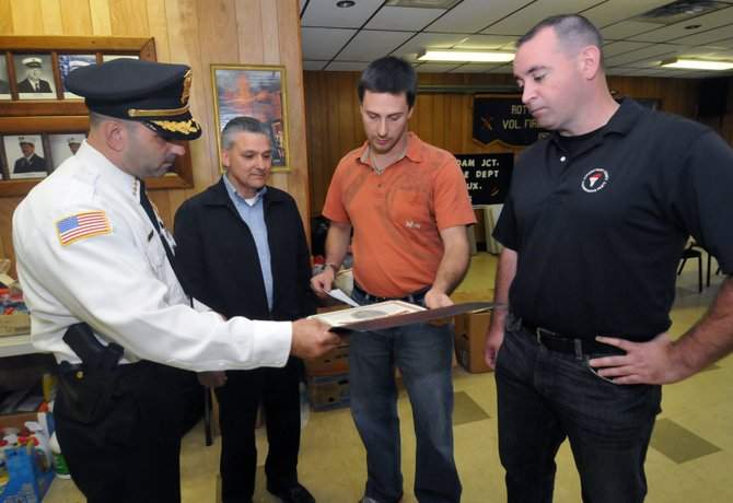 Dominic Dagostino, left, hands over a $1,000 donation on behalf of the Schenectady County Conservative Party to Rotterdam Junction Fire Department Chief Shawn Taylor, as Mike Viscusi looks on with Conservative Club President Robert Hamilton, right.