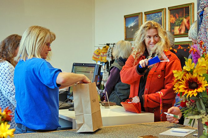 Jennifer Tissot of Saranac Lake (in orange) was the first person to buy merchandise at the Community Store, a community-owned department store that opened its doors in Saranac Lake Saturday, Oct. 29, nine years after Ames went out of business. This village has been without a department store since that time.