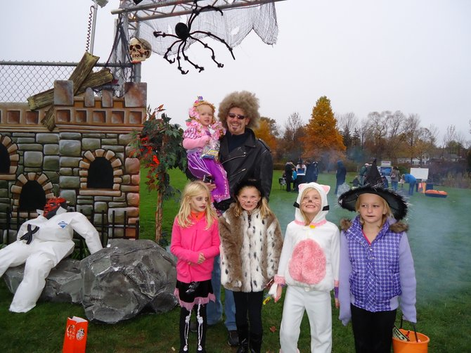 Mark Noble, art director at Eastern Hills Bible Church in Manlius, designed the set behind him for the first annual Ghosts and Goblins Halloween party hosted by the village of Manlius Parks and Recreation Department Saturday at the Manlius Village Centre Pond. From left to right: Melaina Noble 3, Lena Hansen 6, Katya Noble 8, Kaylene Noble, 6, and Nya Hansen, 8.