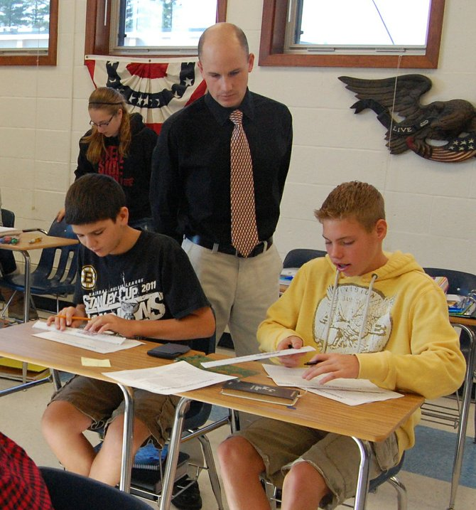 Chazy Central Rural School teacher Justin Frechette works on an immigration project with students in his social studies class earlier this week. The school ranked first in academic rankings in the tri-county area by Business First.