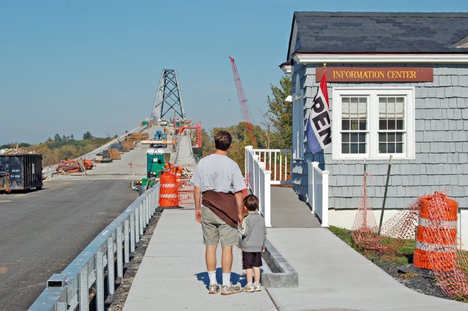 Standing next to the Essex County Visitors Center at Crown Point, a father and son watch Flatiron Construction workers build the Lake Champlain Bridge on Sunday, Oct. 9, the day the bridge was originally slated to open. Due to delays, the bridge is now expected to open Monday, Nov. 7.