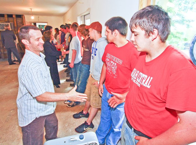 Champlain Valley Tech building trades instructor Kevin Shaw, left, shakes hands with students at the June dedication of the renovated Moriah court house. Classes from Yandon Dillon Educational Center in Mineville built the addition to the court house for the town.