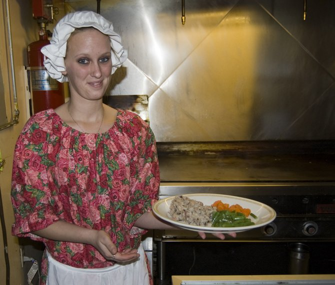 Jessica Aliff, a waitress a the Blue Staff Cafe, holds the dinner offered at Tavern Night as she is dressed in a colonial outfit.