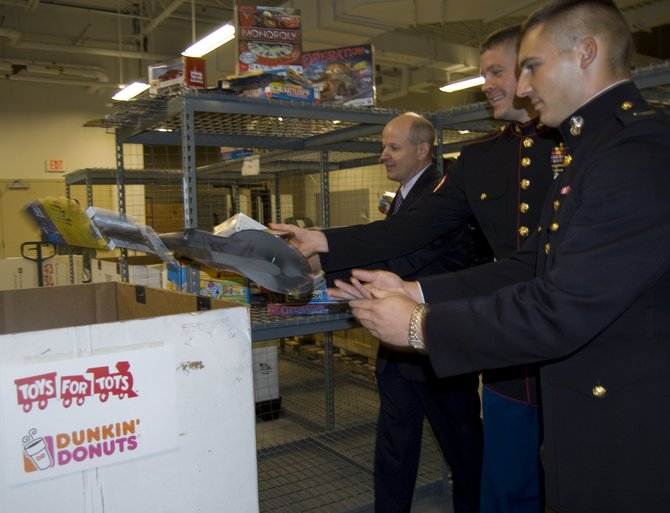From left, Field Marketing Manager for Dunkin' Donuts Eric Stensland, Toys for Tots coordinator Staff Sgt. James Bolen and Second Lt. Marc Mundy help load up donations for Toys for Tots.