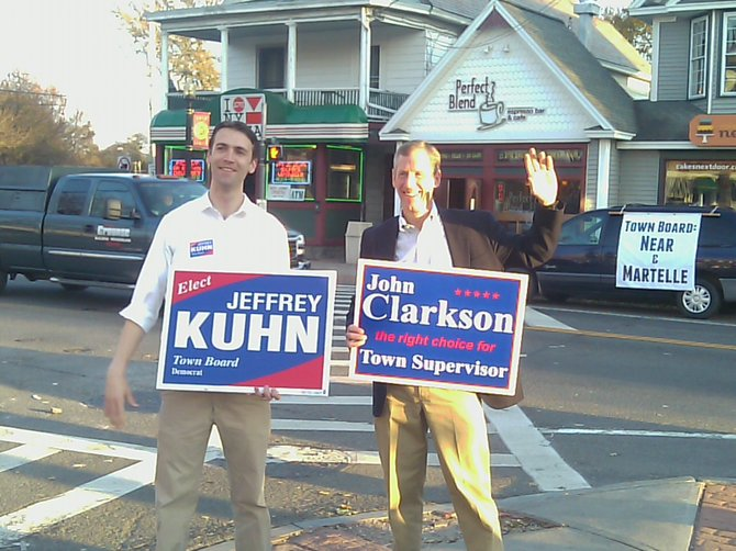 Supervisor candidate John Clarkson and Town Board candidate Jeffrey Kuhn stand at the Four Corners in Delmar late Tuesday afternoon. Across Delaware Avenue, a banner in support of Town Board candidates Jeremy Martelle and Jeremy Near is tied to a van. That van is parked in front of the coffee shop where Clarkson supporters are gathering after the polls close.  