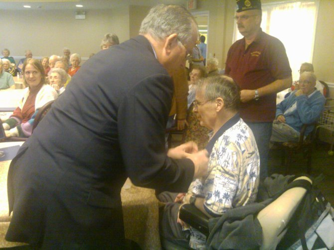 Albany County Executive Michael Breslin gives a pin to Fred Hill, a veteran of the U.S. Army, during a ceremony at the Kenwood Manor senior facility on Thursday, Nov. 10.