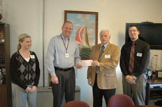 Kinney Drugs Regional Pharmacy Director Rebecca Bubel, Regional Retail Director Dale Myatt and Lake Placid Store Manager Russ Knobel present a check for $1,500 to Alan Jones (second from left), Executive Director of Adirondack Community Action Programs, Inc.