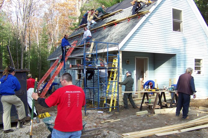 About 65 volunteers from Great Escape and the area Habitat for Humanity chapter work together Friday rehabilitating a home on Birch Avenue in Lake George. The house is to be sold at a discount to a local couple that's for years been living in a garage.