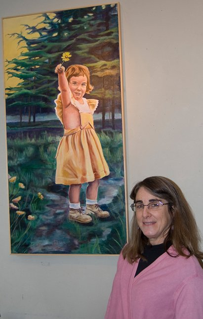 Elizabeth MacFarland stands next to a painting of herself as a little girl, which is included in her art show at the Moon & River Café.