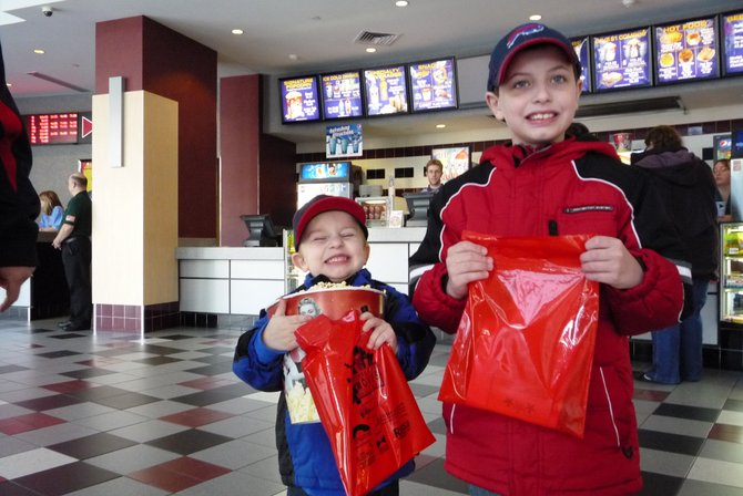 """The early morning screening of """"Puss in Boots"""" on Saturday, Nov. 12, didn't stop kids from grabbing a bucket of popcorn to enjoy."""