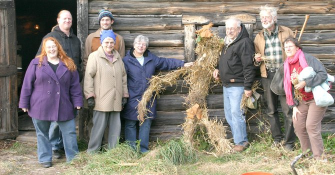 Attendees of the Harvest Home celebration at Baltimore Woods pose outside the nature center's log cabin with the straw manikin they helped create.