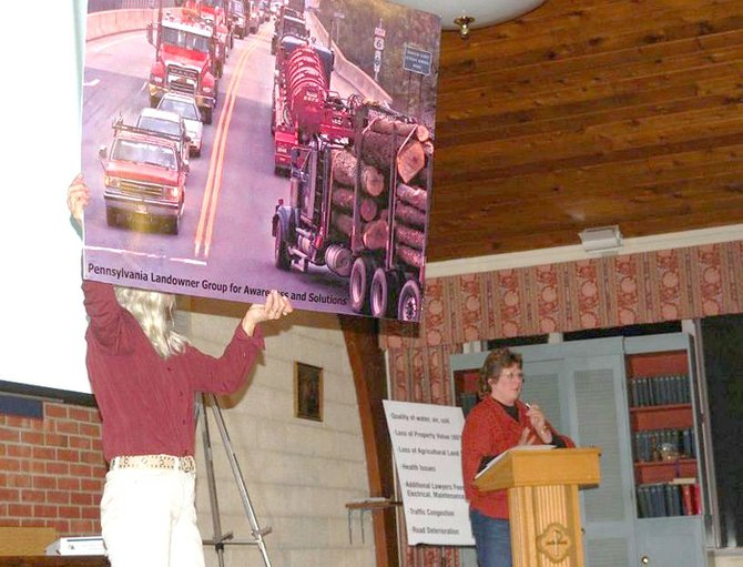Carolyn Knapp holds an enlarged picture which shows a row of heavy commercial traffic brought by the gas industry to Rte 6 in Bradford County, Penn.