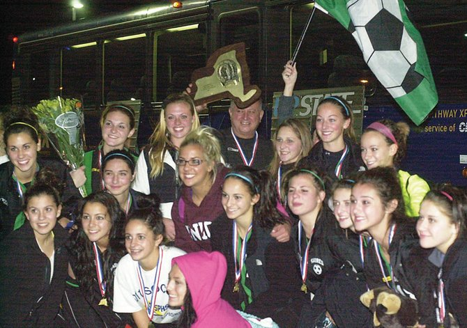 The Schalmont girls soccer team proudly displays its state championship trophy upon its return to the Rotterdam school Sunday night. The Sabres defeated Greece Odyssey (Section V) 4-0 in the Class B finals earlier in the day.
