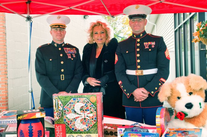Sondra Stephens, center, stands with two marines during last year's Toys for Tots campaign.