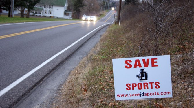 Signs have been placed around the community, urging residents to help save the JD sports program.