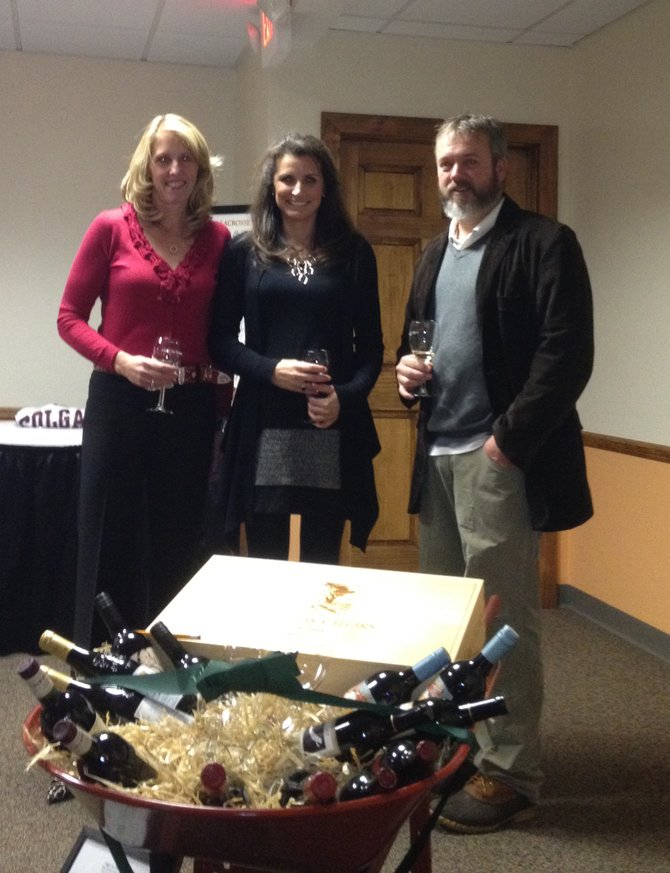Susan Baldwin, left, Kara Connellan and Eric Burrell pose with a wheelbarrow full of wine that Burrell donated for the Light Up Fenner silent auction, Nov. 19. Proceeds from auctioned items were donated to a fund for the installation of field lights at the Sean Googin Sports Complex.