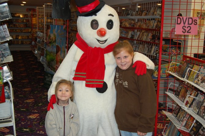 Aubrey(left) and regina Seymour pose for a picture with Frosty the Snowman at Under One Roof Video in Plattsburgh.