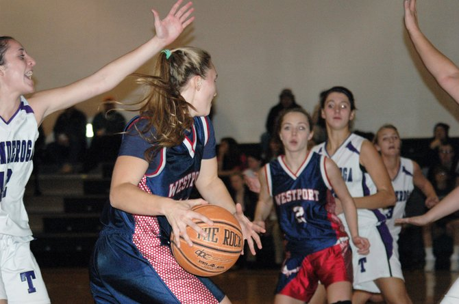 Westport's Willa McKinley drives to the basket as Delany Sears drops into the lane.