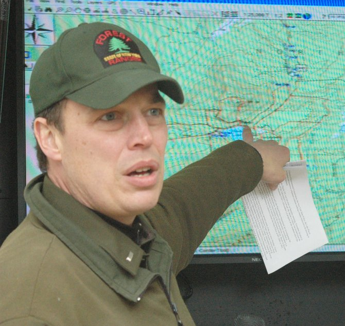 DEC Forest Ranger Lt. Brian Dubay points at a map of the Adirondack Loj region during a search last fall.