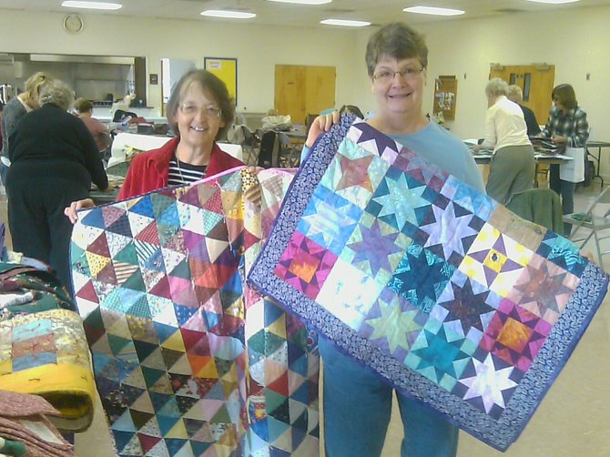 Marylou Wahl (left) and Kathy Riedel (right) hold quilts made by members of Bethlehem Lutheran Church Quilting Friends. The group of 24 women will send out close to 100 quilts to those in need before the end of the year.