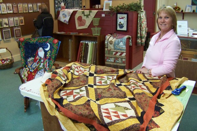 Nancy Hayes, proprietor of Chestertown&#39;s new store Country Girl Crafts &amp; Quilts, takes a moment away her from duties to show off the wide variety of fabrics she has in stock. Open Tuesday  through Saturday, the enterprise also offers sewing machines, patterns and notions.