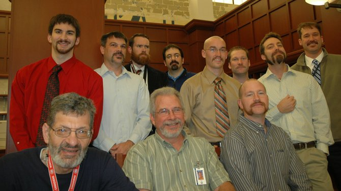 Participants of the Second Annual Tom Selleck Mustache contest pose at the awards ceremony. Sitting from left: George Sturiale, John Behm and Peter Chapman. Standing from left: Michael Mistretta, AS. James Szalach, Josh Williams, Keith Lamphere, Brian Sevey, Jim Ryan, Rob DeMass and Rob Pickup.