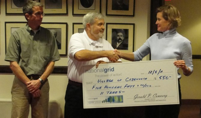 """Jim Maloney, left, and Brian Skinner, of National Grid's Forestry Division, present Cazenovia Deputy Mayor and tree commissioner Amy Mann with a check for $550 through the company's """"10,000 Trees and Growing"""" program, Dec. 5."""