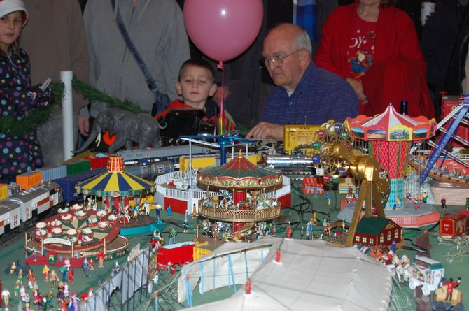Don Erlenbush shows children how to runs the trains on his circus display at the Saratoga Festival of Trees.