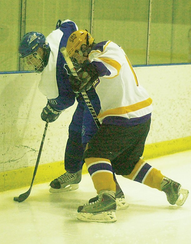 Christian Brothers Academy's Chris O'Keefe, right, ties up a Saratoga player along the boards during last Saturday's Capital District High School Hockey League game at the Albany County Hockey Facility in Colonie.