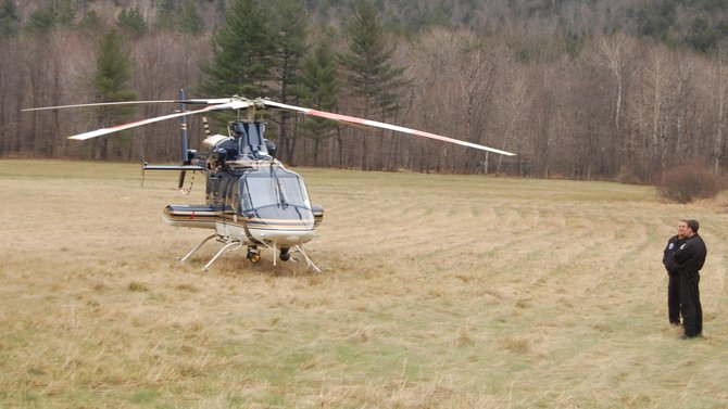 Officers William Accousti and C.J. Clark wait for mechanics to inspect the Bell 430 twin engine helicopter in a field off of Rte. 9N in Keene Valley.