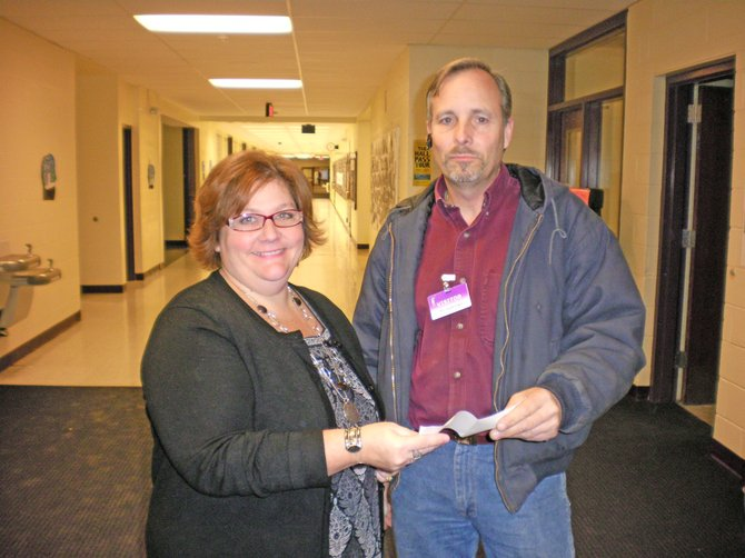 Nancy Quesnel, director of the Tiny Tim Christmas Wish Program, accepts a $3,000 donation from Lowe's. Presenting the check is Anthony Clemons.