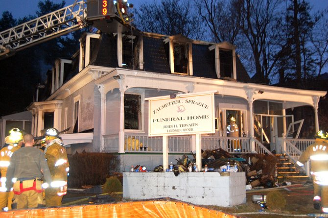 Firefighters work to extinguish the fire at the funeral home.