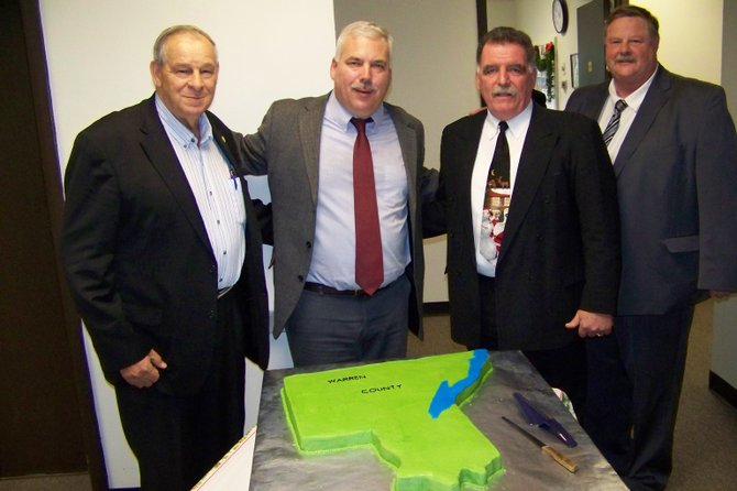 Outgoing Warren County Supervisors pose Dec. 16 behind a cake shaped like Warren County, baked as a gesture of their service to area citizens, presented to them after their last public meeting theyll be presiding over. The cake was baked by thurman Supervisor Evelyn Wood.
