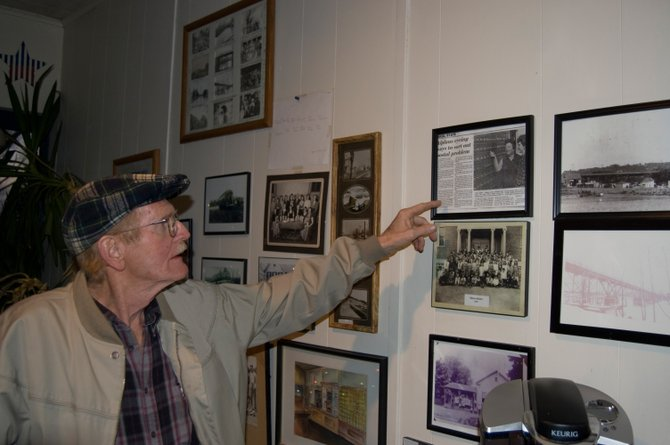 Alplaus resident Cliff Hayes talks about the history of the Alplaus Post Office while pointing to old news stories and pictures hanging on the walls of the office.