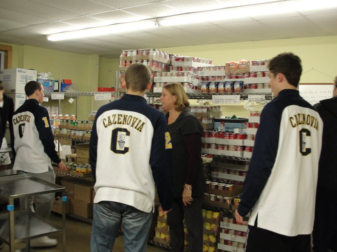 CazCares Director of Client Services Gigi Redmond, center, instructs members of the Cazenovia varsity boys basketball team what boxes to move, Dec. 14 in the food pantry.