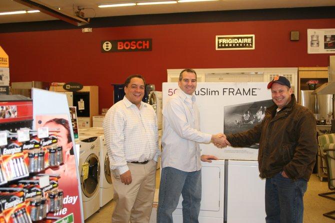 Earl Buyea, Jr., left, of Buyea's True Value, looks on as Cazenovia Lions Club President Tim Taber awards raffle winner Scott Griffin a new 50-inch plasma television.