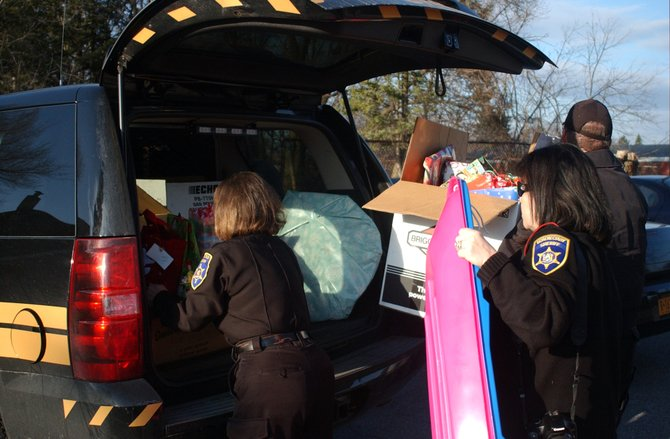 Employees of the Schenectady County Sheriff's Office unload presents on Tuesday, Dec. 13, before surprising children at the Rotterdam Boys & Girls Club with the gifts.