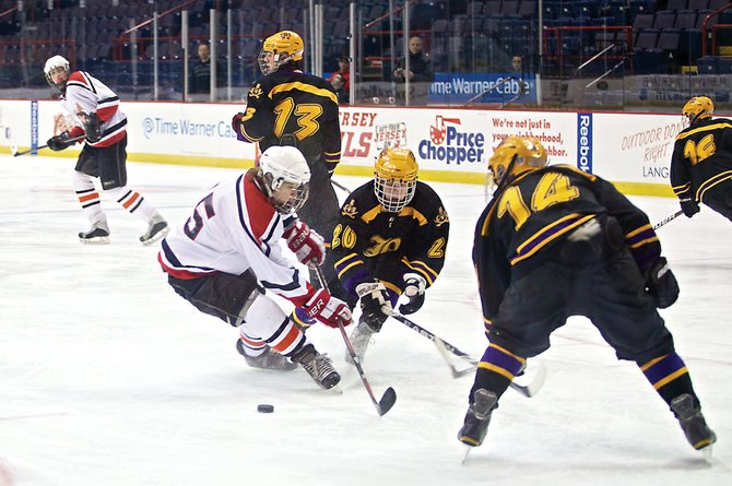 Guilderland/Mohonasen's Aaron Hull, left, has the puck poked away by Christian Brothers Academy's Sean Glennon (20) during Saturday's Capital District High School Hockey League game at Albany's Times Union Center.