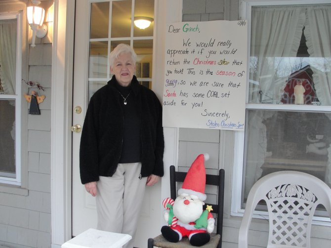 "Nancy Stoker poses with the letter her daughter Joan penned to the ""Grinch"" who stole their shining star decoration outside their house on Farnham Street."