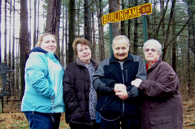 "Longtime Lake George Village Sewer Plant Superintendent Reggie Burlingame (second from right) poses with family members in front of a road sign that was unveiled Dec. 23. The village re-dedicated the village road leading to the sewer plant as ""Burlingame Boulevard,"" honoring Burlingame's 22 years of service. Among the 40 or so village employees and family members attending the ceremony were (left to right) Reggie's daughter Tiffini Burlingame, his wife Elly Burlingame, Reggie Burlingame, and his mother-in-law Shirley Sipos."