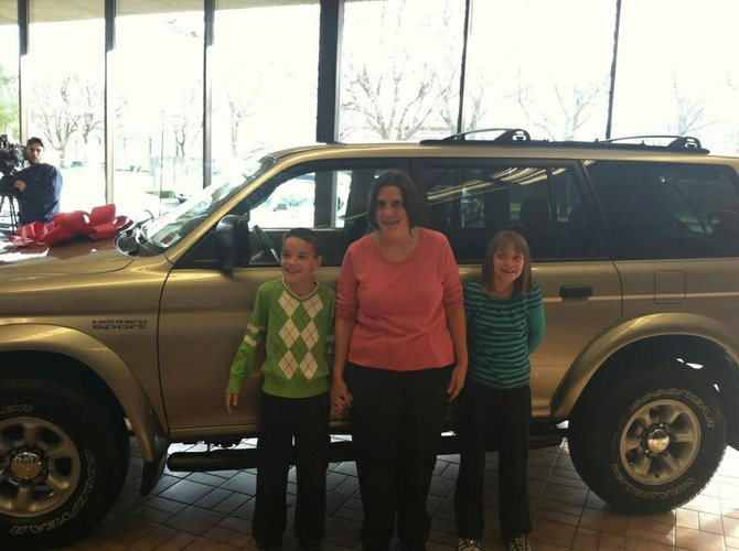 Joyce C. Nichols of Colonie received a 1997 Mitsubishi Montero as part of a contest held by Otto Cadillac on Central Avenue. The car will make life with her third grade twins Brandon, left, and Krista, right, much easier. Otto Cadillac will also pay for the plates, registration and 8 percent sales tax that would normally fall on Nichols shoulders.
