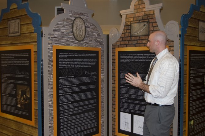 "Ryan Mahoney, curator of the Schenectady County Historical Society, discusses a panel featured in the traveling exhibit ""Light on New Netherlands,"" which is hosted at the new education center at Mabee Farm."