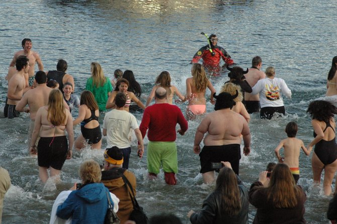 Drawn by balmy temperatures to the annual Lake George New Year's Day Polar Plunge, about 2,000 revelers took to the 34-degree lakewaters in three waves of swimmers.