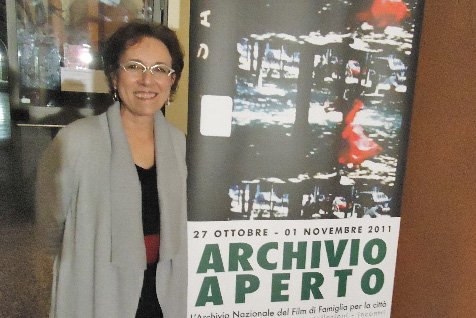 Emily Rossi-Snook stands next to a poster announcing the Archivio Nazionale del Film di Famiglia film festival.