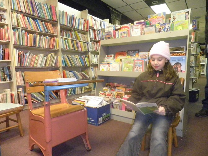 Eight-year old Briana Benson from Stillwater enjoys a book in the Kids Korner of the Book Barn in Latham.