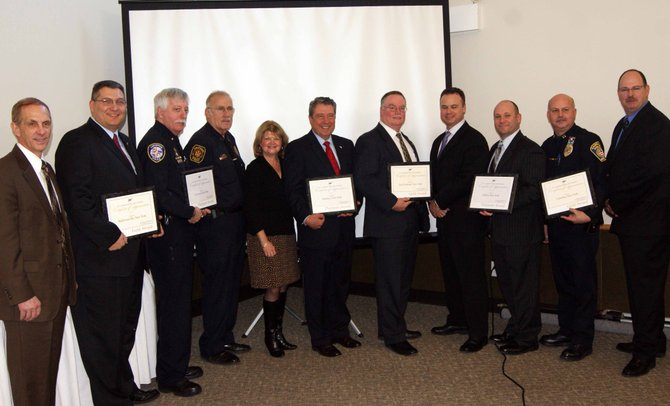 Wally Smith, of AAA, stands with this year's recipients of the Community Traffic Safety Awards: Baldwinsville Police, Liverpool Police, Manlius Police (and town representatives), East Syracuse Police, DeWitt Police and Camillus Police.