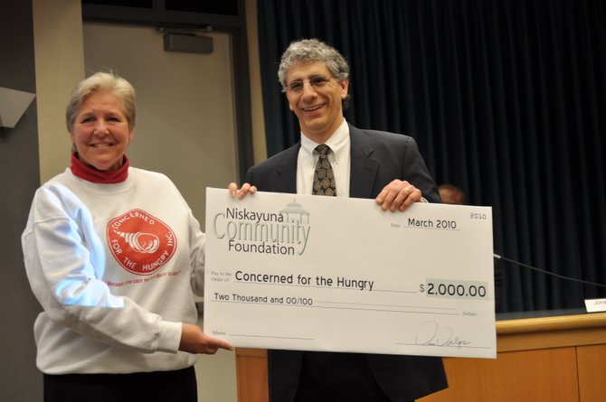 Former Niskayuna Community Foundation president Vince Valenza, right, presents a $2,000 check to a representative of Concerned for the Hungry during a previous grant award ceremony.