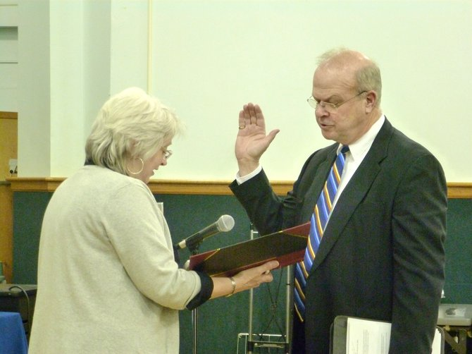 Newly appointed town board member George Lenhardt is sworn in at Wednesday's meeting.