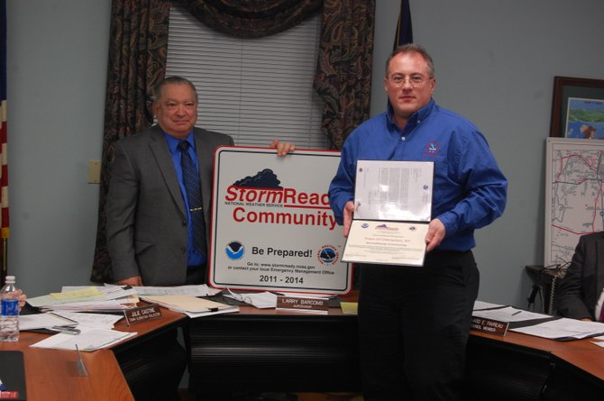 Champlain Town Supervisor Larry Barcomb ( left) receives a Storm Ready sign and certificate from Andy Nash, meteorologist-in-charge at the National Weather Service, Burlington.