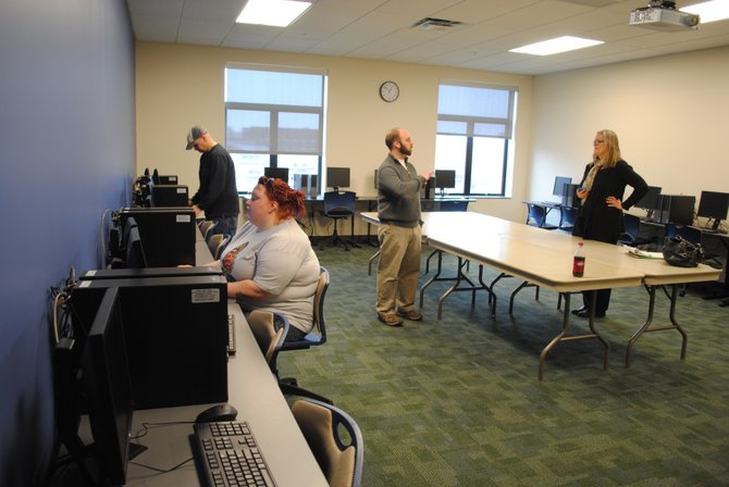 Kelli Hennessey, a liberal arts major from Benson, works on a P.C. in the computer lab while student Greg Lambert and Christ Ettori and Robin Dutcher prepare the space for first day of class, Jan. 23.